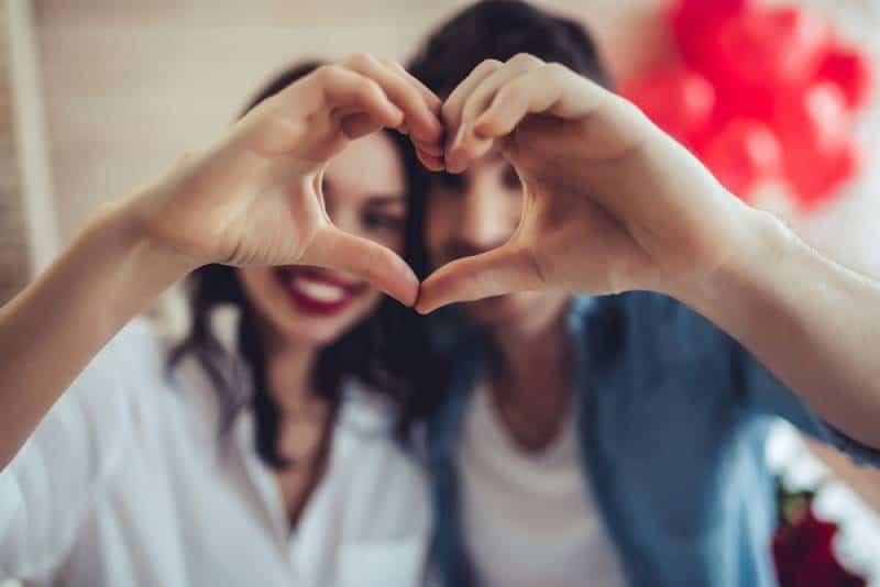 couples heureux à la maison faisant signe de coeur avec des mains