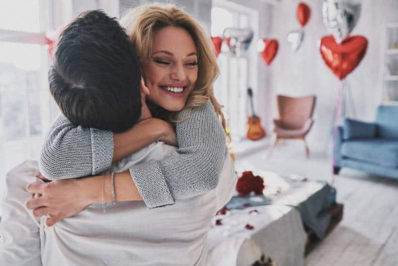 couples heureux étreignant à la maison