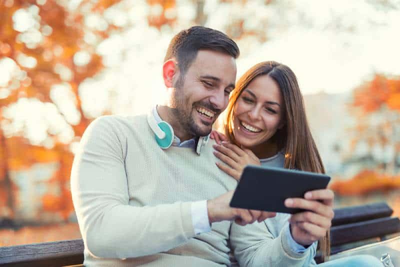 couples heureux s'asseyant sur un banc dans le stationnement à l'automne
