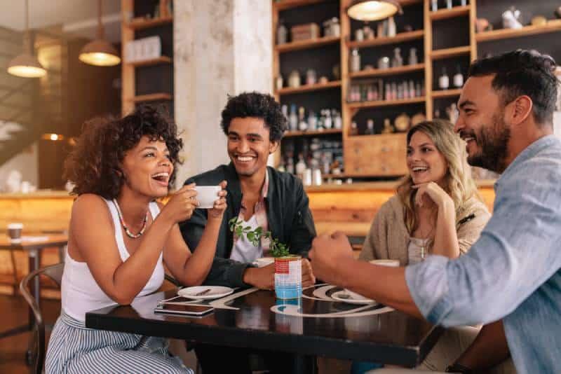 des jeunes assis dans un café et souriant.