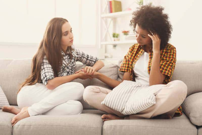 deux femmes parlent de leurs problèmes alors qu'elles sont assises sur un canapé à la maison