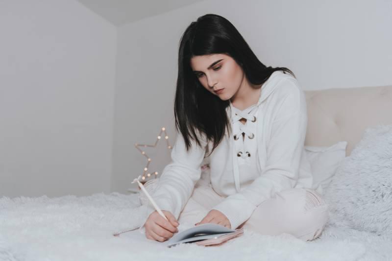 femme écrivant une lettre dans sa chambre