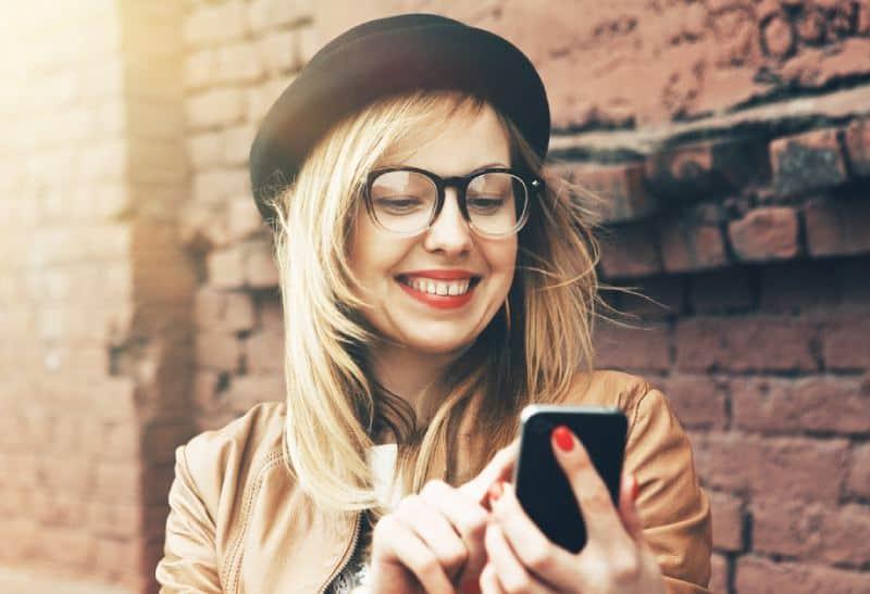 femme de sourire tapant sur son téléphone à l'extérieur