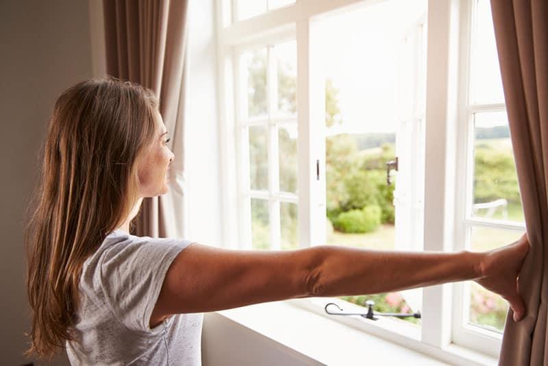 femme, debout, fenêtre, chambre à coucher