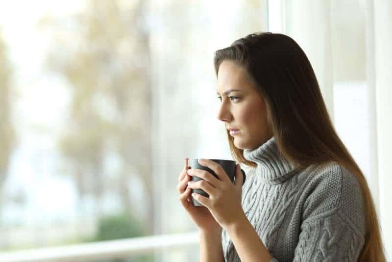 femme pensante tenant une tasse de thé et regardant dehors
