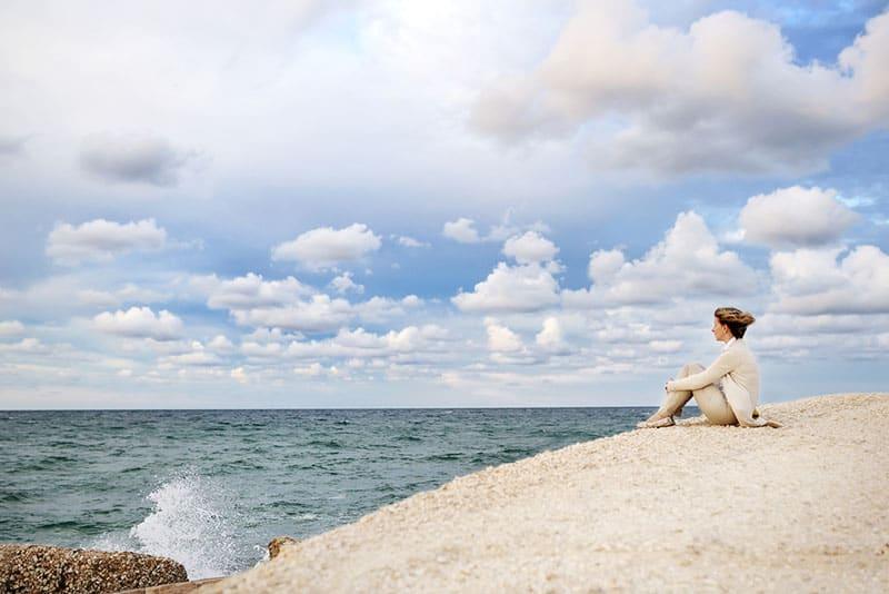 femme solitaire assis au bord de la mer
