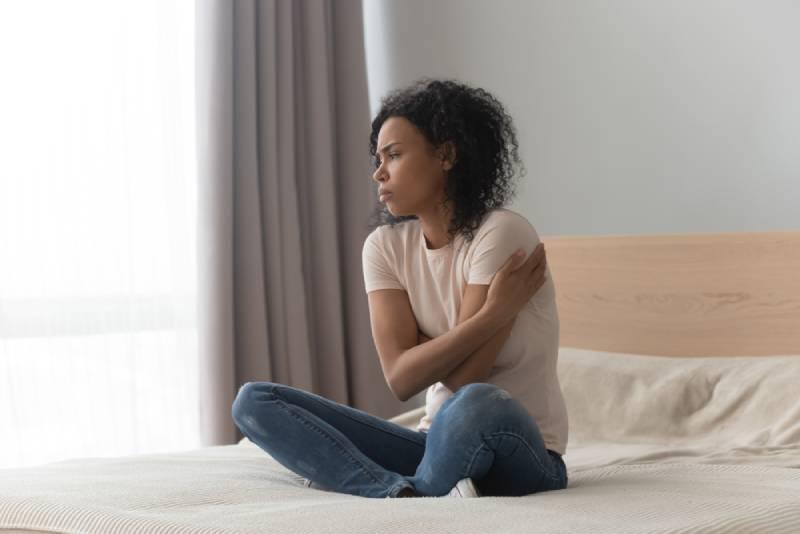 femme triste assise dans son lit, seule à la maison