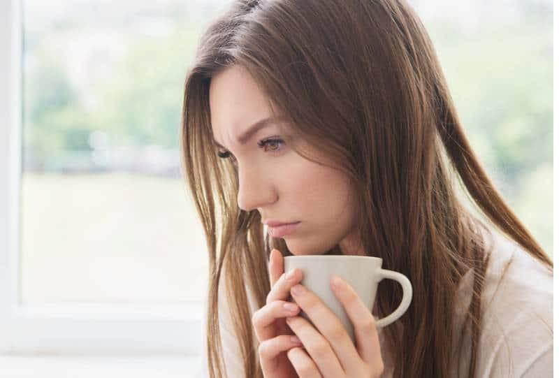 femme triste en pensant et en rentrant chez elle et en tenant une tasse de