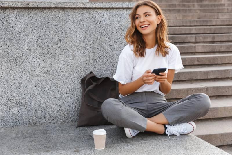 fille de sourire s'asseyant dehors et retenant le téléphone