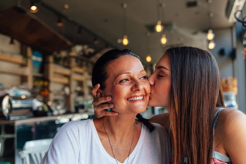 fille embrassant sa mère dans la joue