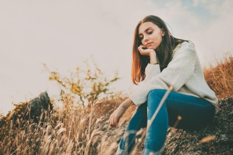 fille inquiète dans l'herbe