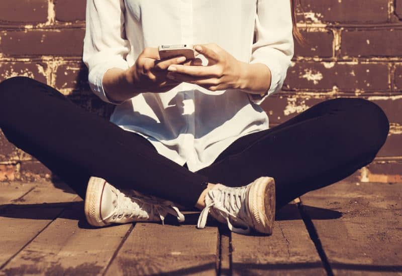 fille s'asseyant sur le trottoir et tapant le message sur le téléphone