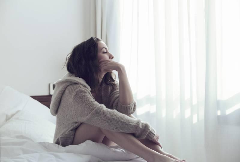 fille triste assise dans sa chambre et regardant par la fenêtre