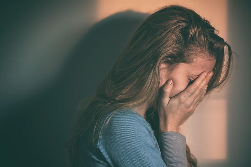 fille triste pleurer avec les mains sur le visage