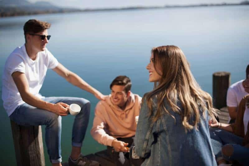 groupe d'amis assis sur un quai de bateau