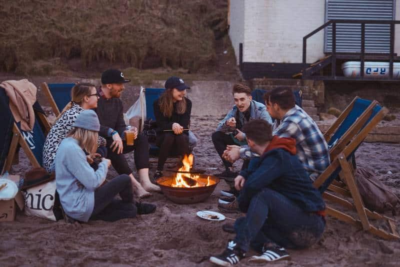 groupe de personnes assises devant un feu