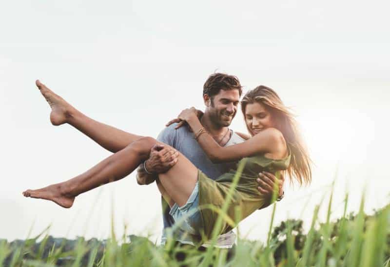 homme portant sa belle petite amie dans la nature