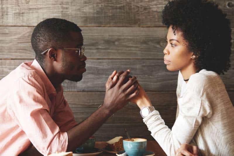 homme s'excusant auprès de la femme au café