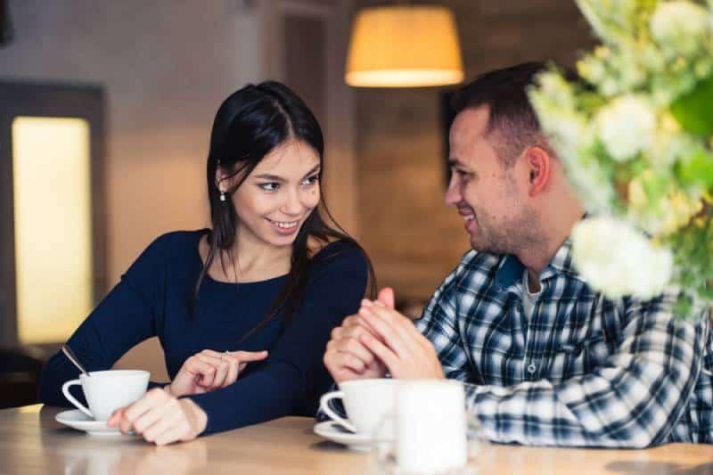 jeune couple discutant au café