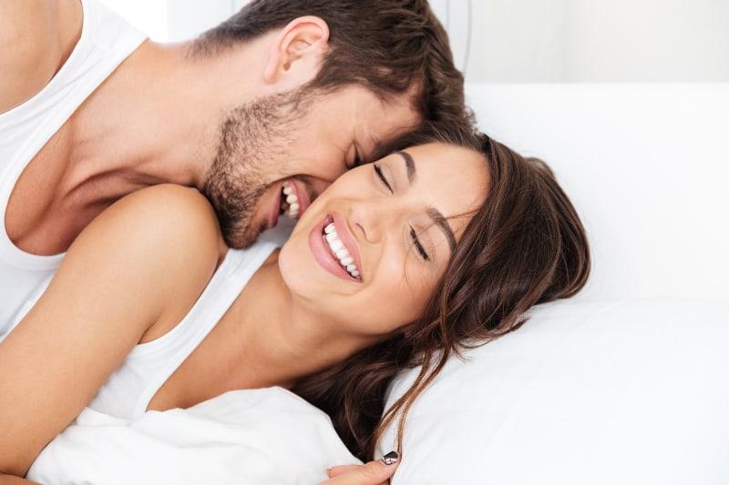jeune couple souriant sur son lit