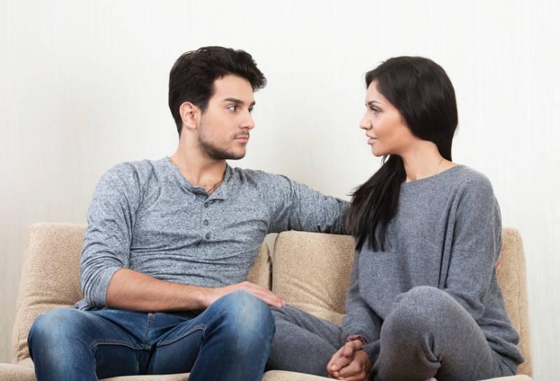 jeune couples s'asseyant au sofa dans le salon