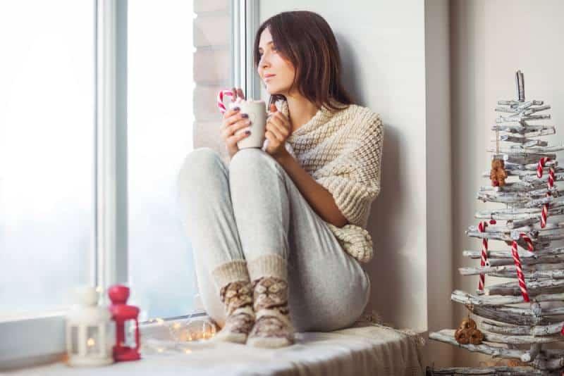 jeune femme assise à la fenêtre et buvant du café