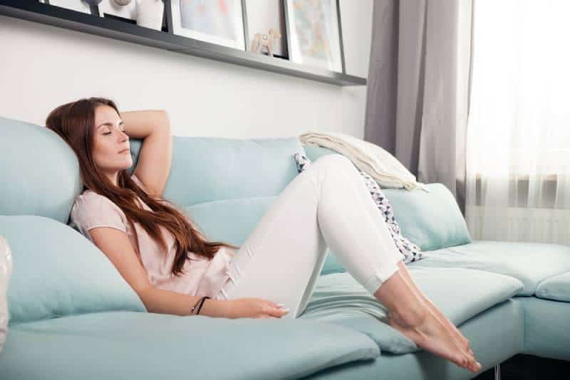 jeune femme heureuse allongée dans le salon et se détendant