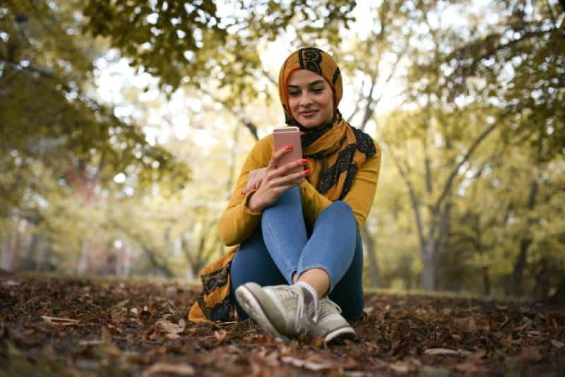 jeune femme heureuse, assise dans la forêt et tapant au téléphone