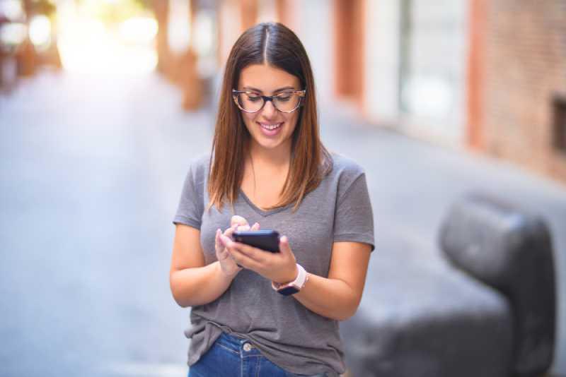 jeune femme heureuse envoyant des SMS au téléphone à l'extérieur