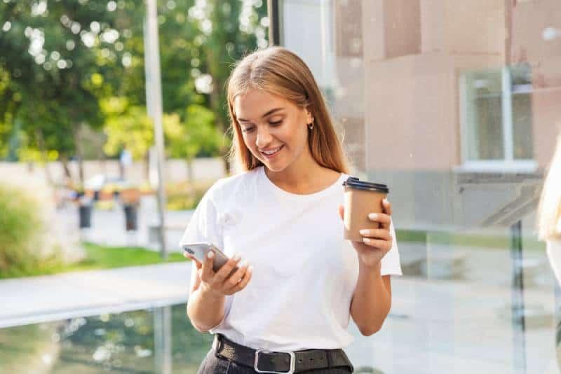 jeune femme positive utilisant le téléphone portable à l'extérieur