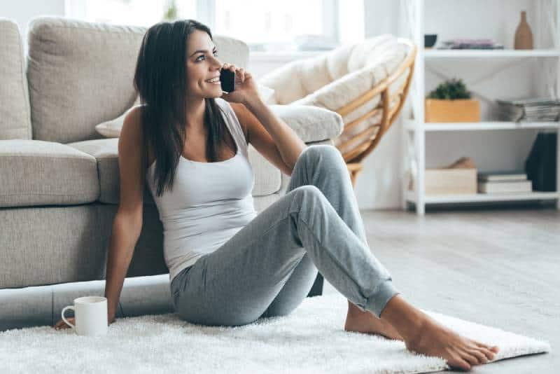 jeune femme s'asseyant au plancher dans le salon et parlant au téléphone