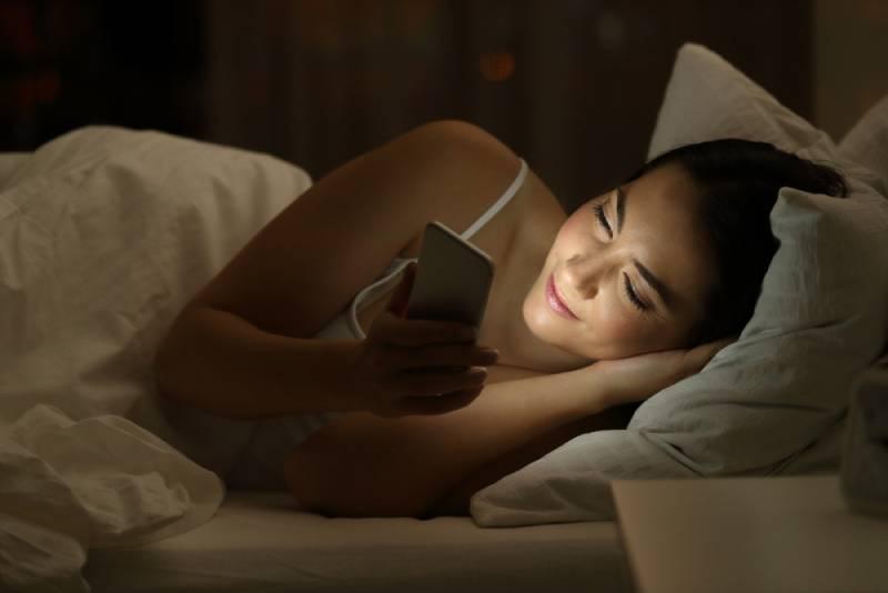 jeune fille heureuse utilisant le téléphone avant le sommeil
