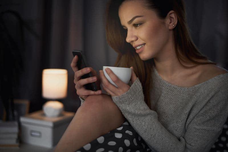 jeune fille regardant son téléphone dans la chambre à coucher
