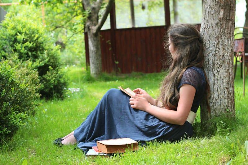 la jeune fille assise sous l'arbre et écrivant une lettre