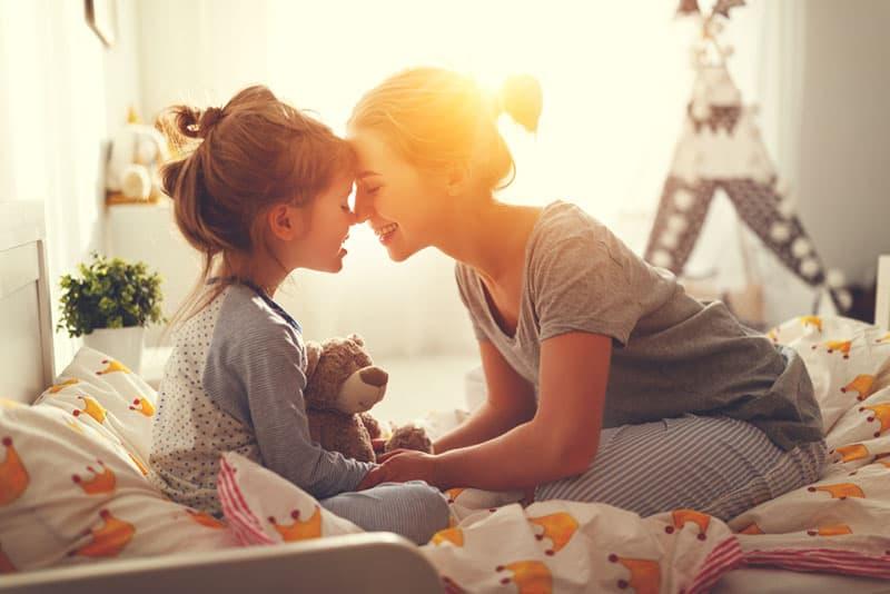 mère embrassant sa petite fille sur le lit