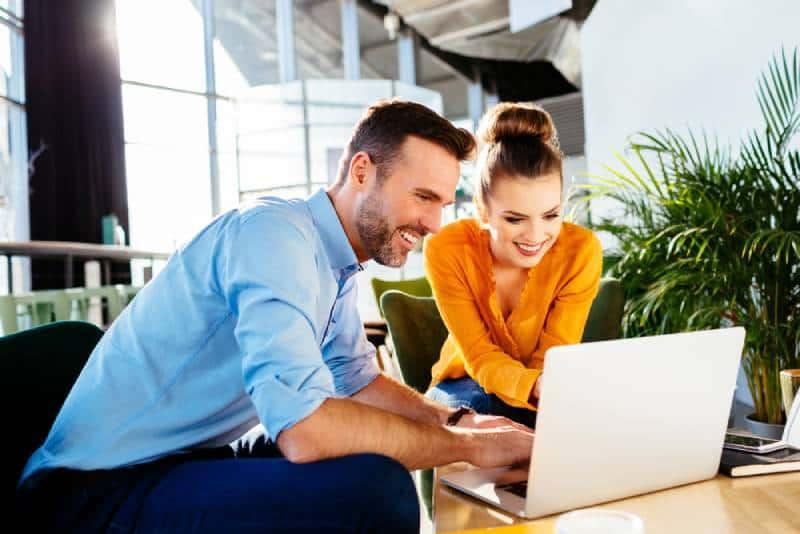 travailleurs souriants regardant l'écran d'ordinateur portatif au bureau
