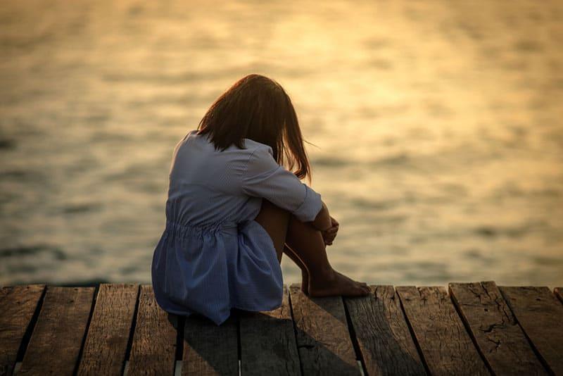 triste jeune femme assise sur le coucher de soleil au bord de la mer