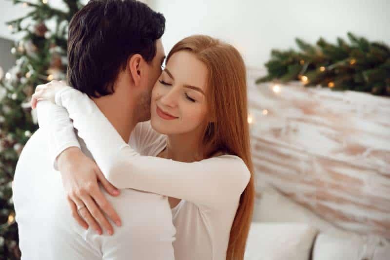 un couple s'embrasse en amoureux près de l'arbre de Noël