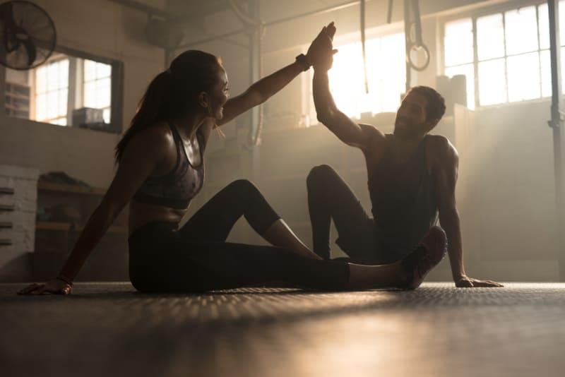 un homme et une femme assis par terre et se donnant des high-five à la salle de sport