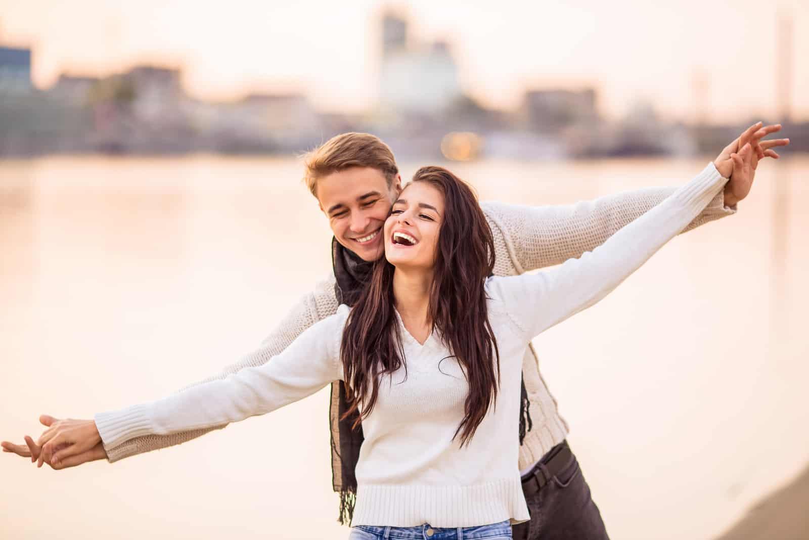 un homme et une femme se tiennent les bras tendus