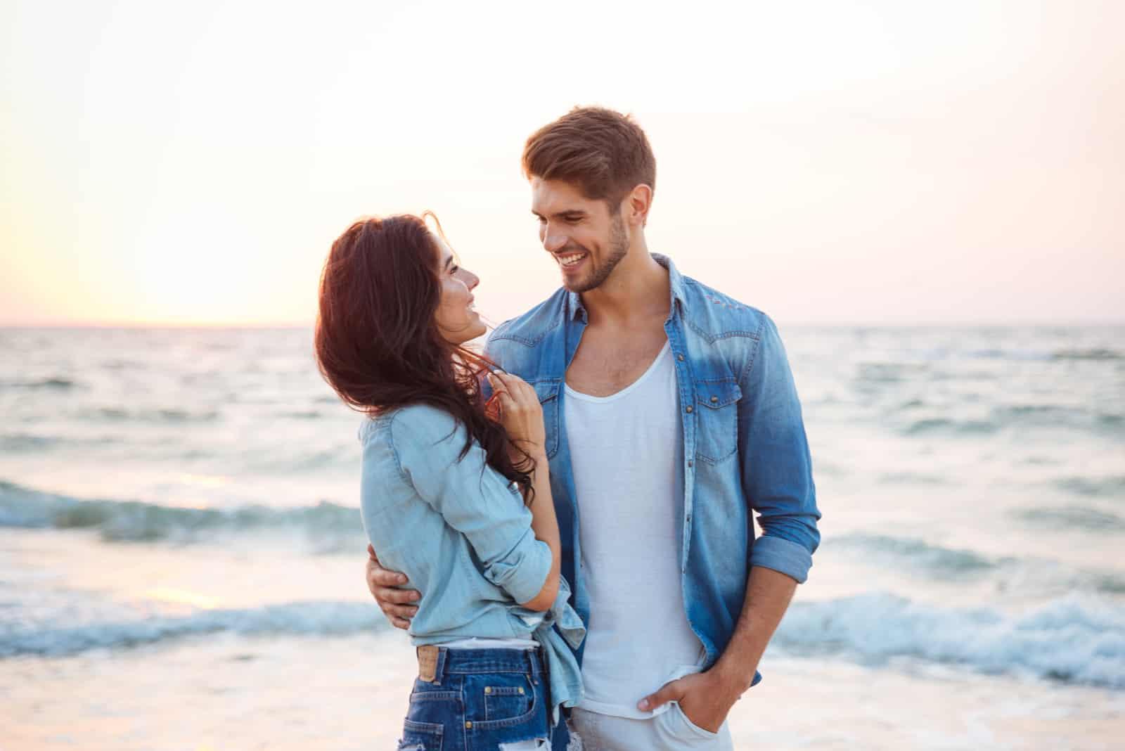 un homme et une femme s'embrassent au bord de la mer