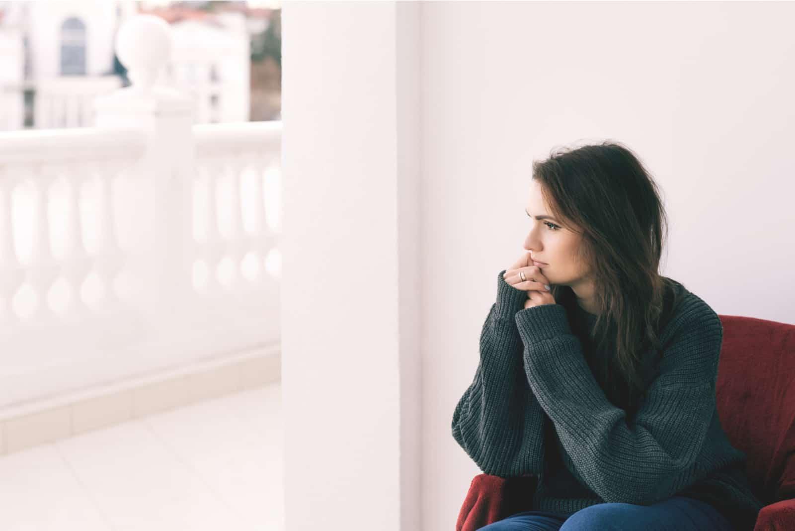 une femme triste est assise dans un fauteuil et regarde par la fenêtre