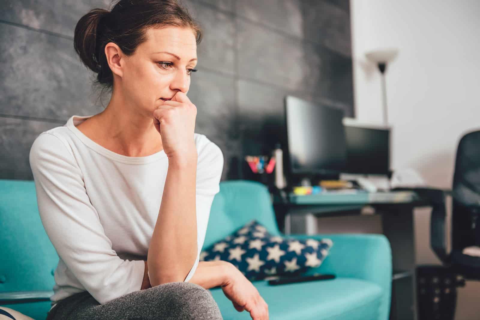 une femme triste pleure sur le canapé