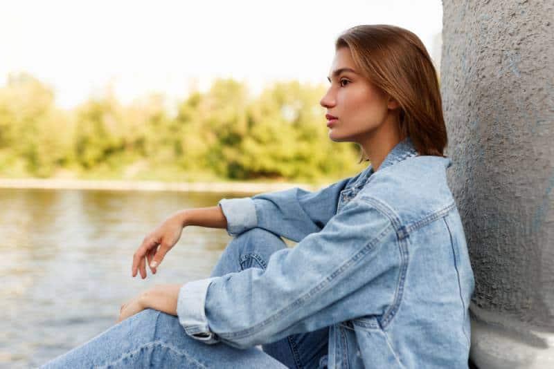une fille célibataire sérieuse en mer près d'une rivière