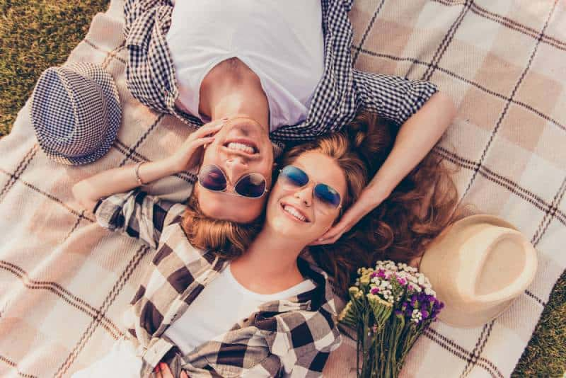 vue de dessus d'un couple d'amoureux allongé sur un plaid de pique-nique