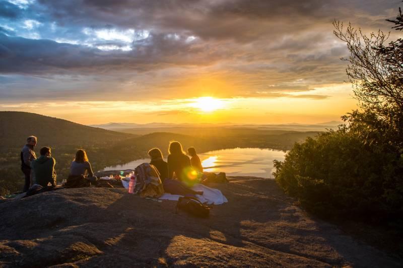 un groupe de personnes se dirigeant vers le soleil couchant