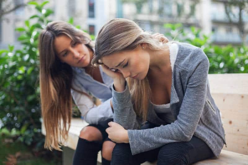 Ami donnant du soutien à des amis à l'extérieur sur un banc de parc