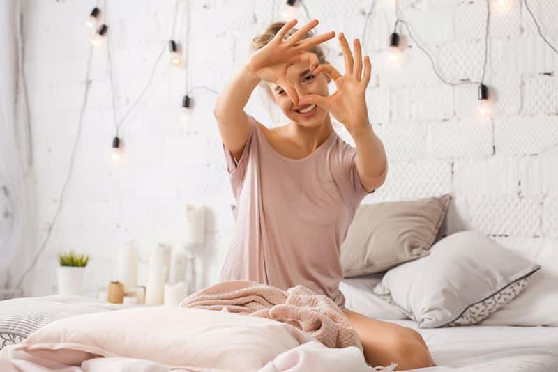 femme heureuse faisant un coeur avec les mains