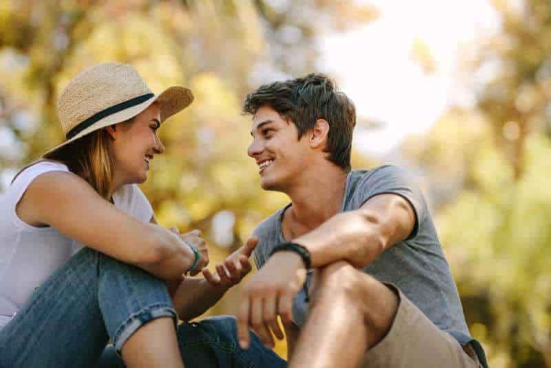 Un homme et une femme en pique-nique, assis dans un parc, se parlent