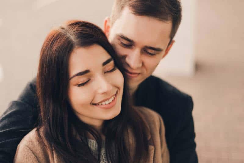 Un couple d'amoureux s'embrasse dans la rue.